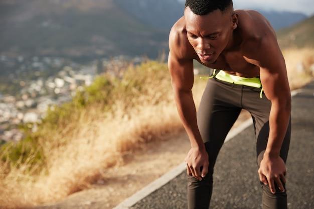 Hombre atlético de alta velocidad con piel oscura saludable, trota fuera de la ciudad, recupera el aliento, se siente cansado de un entrenamiento agotador, quiere estar en forma, ha corrido. estilo de vida saludable, etnia y cansancio.