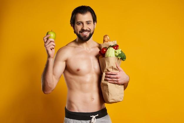 Hombre atlético con bolsa de papel de productos frescos tiene manzana
