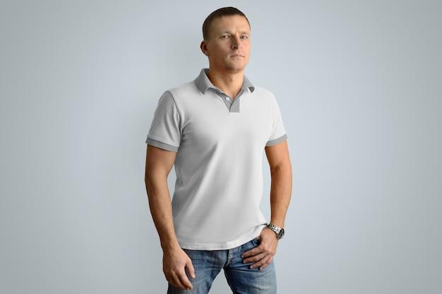 Hombre atlético en la camisa de polo en blanco y jeans con la mano en el bolsillo aislado en la pared gris, vista en ángulo frontal.