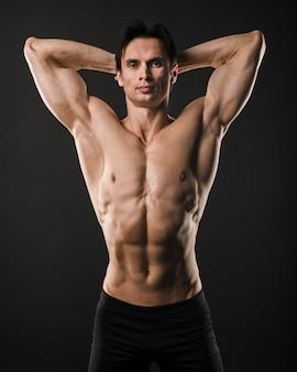 Hombre atlético sin camisa posando con los brazos arriba