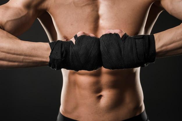 Hombre atlético sin camisa posando con guantes de boxeo