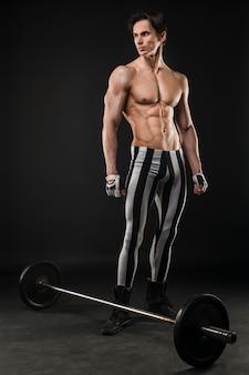 Hombre atlético sin camisa posando con juego de pesas
