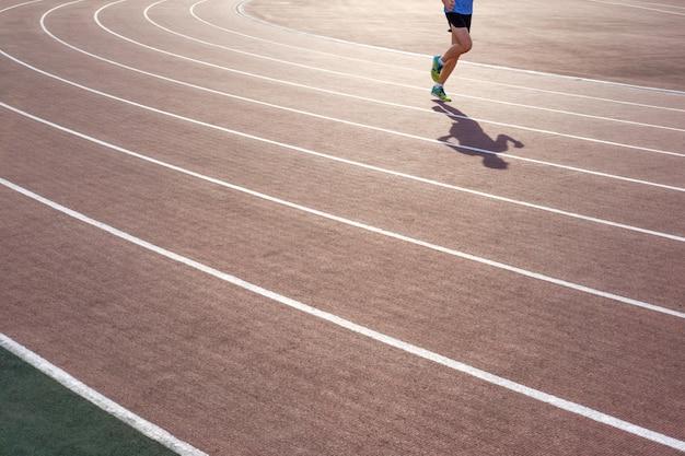 Hombre atlético en coloridas zapatillas de correr en el estadio de atletismo