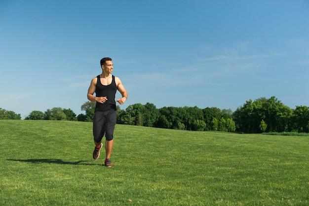 Hombre atlético corriendo al aire libre en un parque