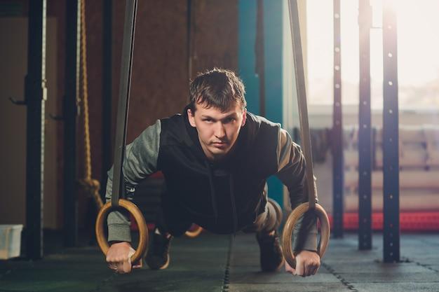 Hombre atlético ejercicio muscular haciendo ejercicio intenso en el gimnasio en anillos de gimnasia.