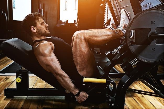 Hombre atlético entrena piernas en el simulador en el gimnasio con peso. cuerpo atlético, estilo de vida saludable, motivación física, cuerpo positivo.
