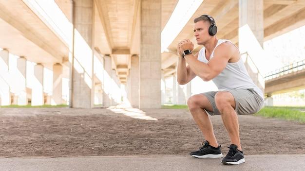 Hombre atlético entrenando afuera con espacio de copia