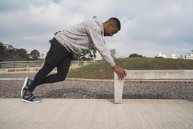 Hombre atlético estiramiento antes del ejercicio.