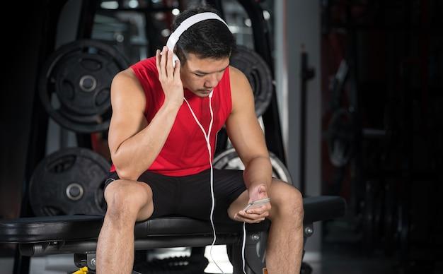 Hombre atlético guapo de deportes escuchando música con auriculares en el gimnasio en el interior