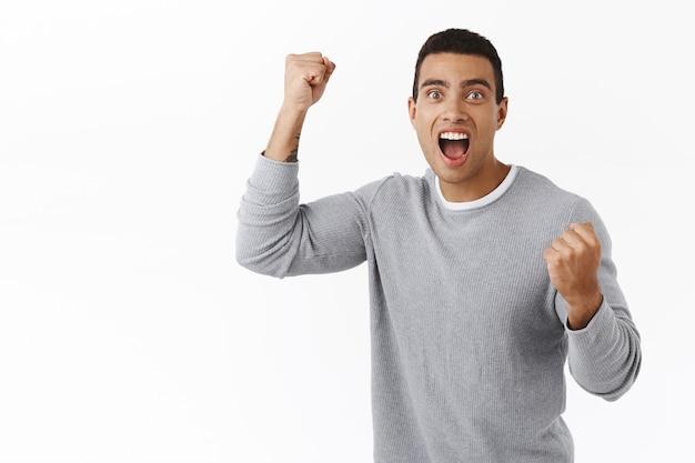 Hombre atlético guapo emocionado, optimista y regocijado cantando, levantando la mano en hurra