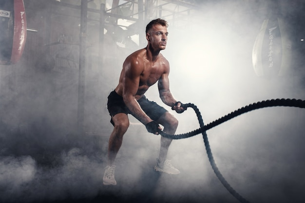 Hombre atlético haciendo ejercicios de crossfit con cuerda en el gimnasio ahumado