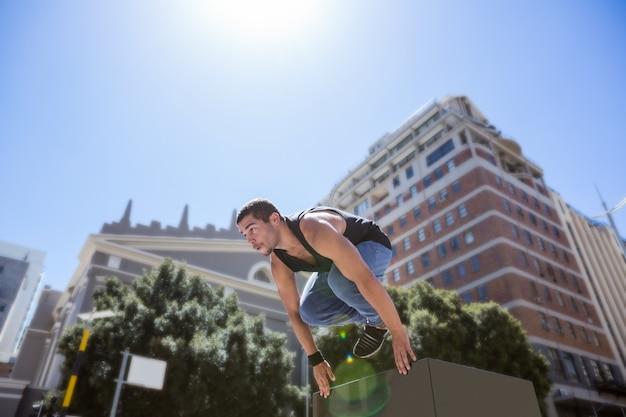 Hombre atlético haciendo parkour en la ciudad