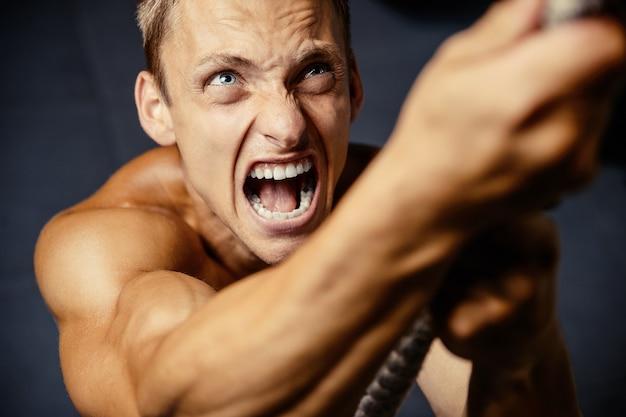 Hombre atlético joven que bombea los músculos en el gimnasio en el concepto del deporte y del cuidado de la salud del entrenamiento