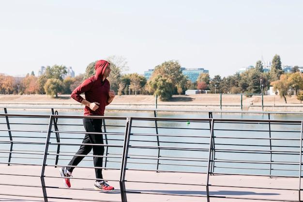 Hombre atlético joven en la sudadera con capucha de la sudadera que corre en el parque