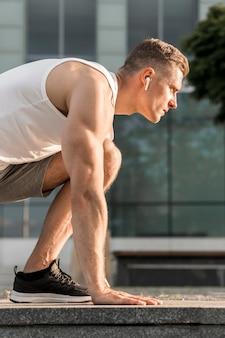 Hombre atlético lateralmente entrenando afuera