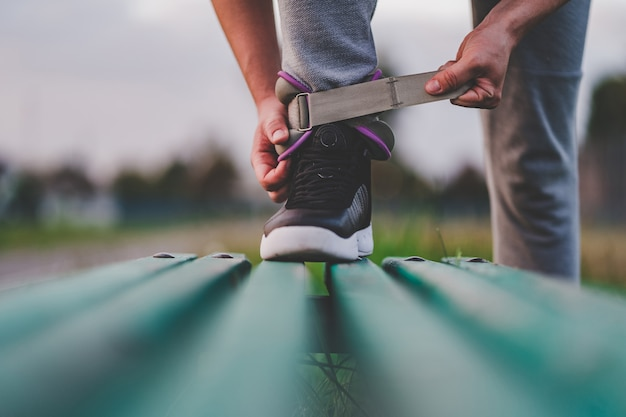 Hombre atlético pone pesas deportivas para caminar durante el entrenamiento al aire libre. estilo de vida saludable y deportivo.