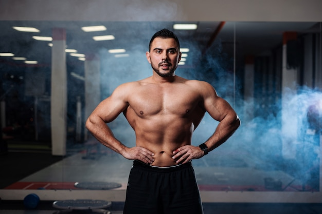 Hombre atlético posando, mostrando sus músculos en el gimnasio.