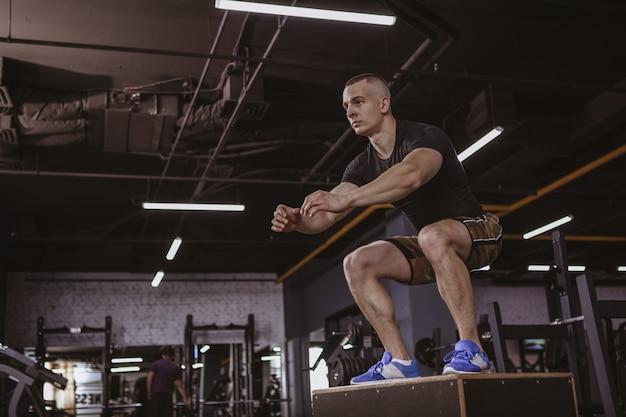 Hombre atlético realizando entrenamiento de crossfit en el cuadro de crossfit