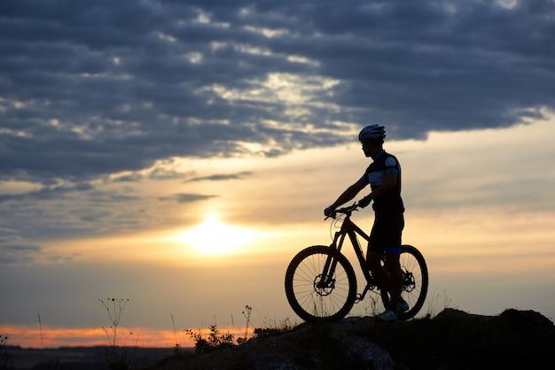 Hombre atlético en ropa deportiva y casco cogidos de la mano en bicicleta y de pie cerca de él. ciclista enérgico posando en el crepúsculo y la puesta de sol en la colina y contra el maravilloso fondo de cielo y nubes.