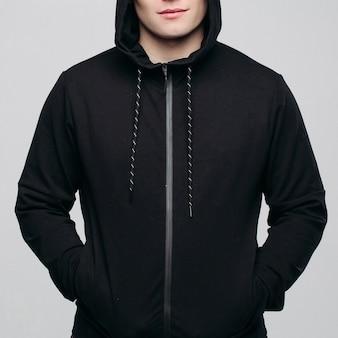 Hombre atlético serio en negro con capucha.