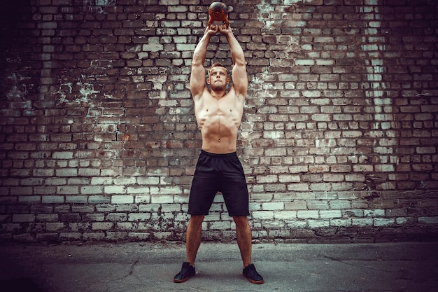 Hombre atlético trabajando con pesas rusas. fuerza y motivación