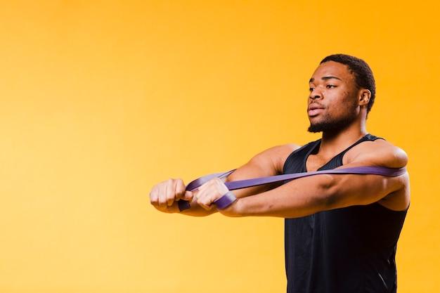 Hombre atlético en traje de gimnasio con banda de resistencia y espacio de copia