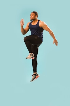Hombre atlético en traje de gimnasio saltando