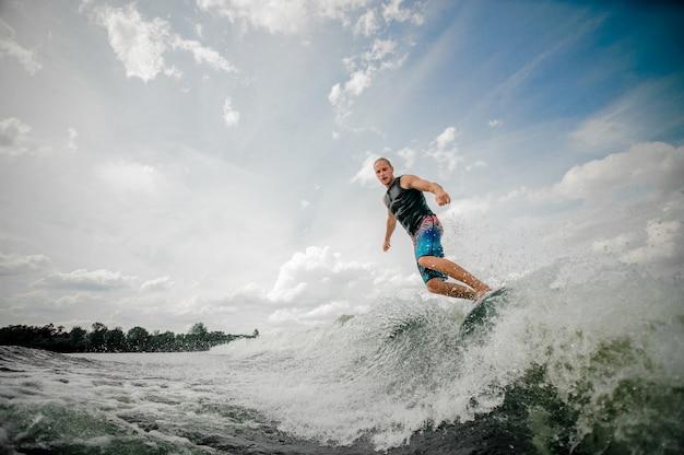 Hombre atlético wakesurfing en el tablero río abajo contra el cielo