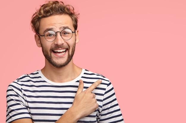 Hombre atractivo sin afeitar con peinado rizado, mira positivamente y apunta a copyspace