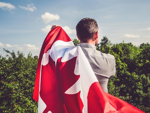 Hombre atractivo con bandera canadiense. fiesta nacional