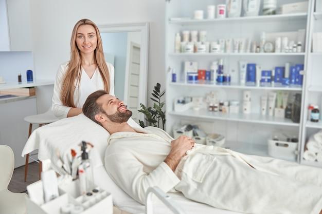 Hombre atractivo con barba está acostado boca arriba, antes de un masaje de estiramiento facial. tratamiento de belleza de masaje facial. concepto de bienestar, belleza y relajación.