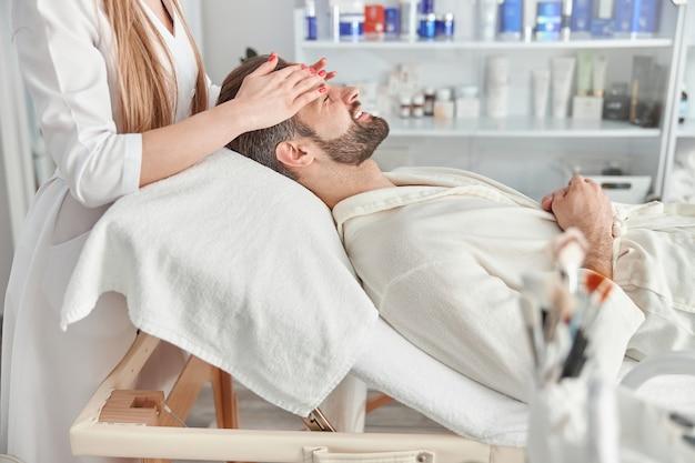 Hombre atractivo con barba está acostado boca arriba, recibiendo un masaje de estiramiento facial. tratamiento de belleza de masaje facial. concepto de bienestar, belleza y relajación.