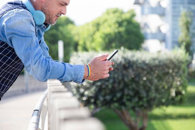 Hombre atractivo con brazalete de bandera gay sosteniendo un teléfono inteligente