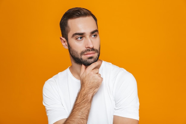 Hombre atractivo en camiseta tocando su barbilla mientras está de pie, aislado en amarillo
