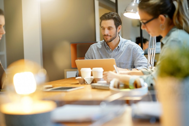 Hombre atractivo en la computadora portátil en el espacio de trabajo co
