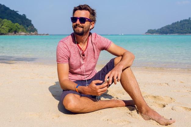 Hombre atractivo feliz en elegantes gafas de sol con barba mediante teléfono móvil en la playa