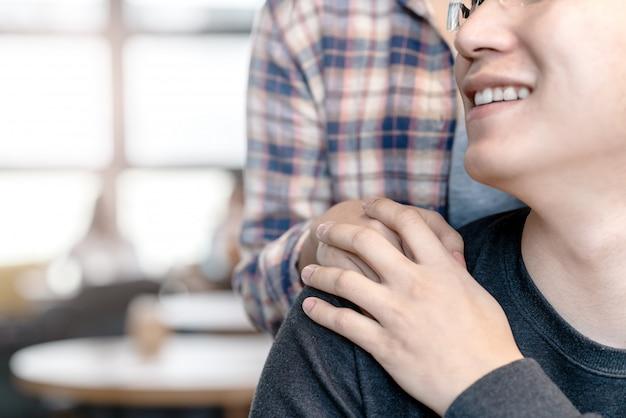 Hombre atractivo feliz joven y mujer asiáticos que llevan a cabo las manos