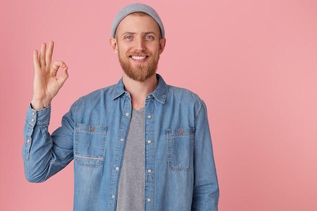 Hombre atractivo feliz con sombrero gris, con expresión facial satisfecha, muestra signo bien, se siente feliz después de hacer un trato, aislado. expresiones faciales humanas, lenguaje corporal.