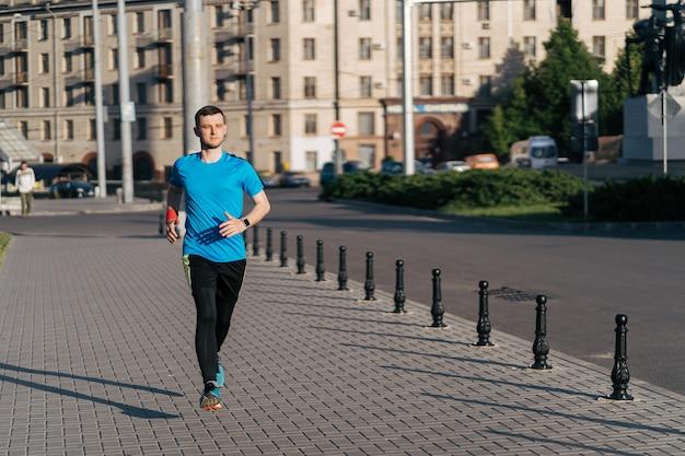 Hombre atractivo en forma corriendo en la ciudad