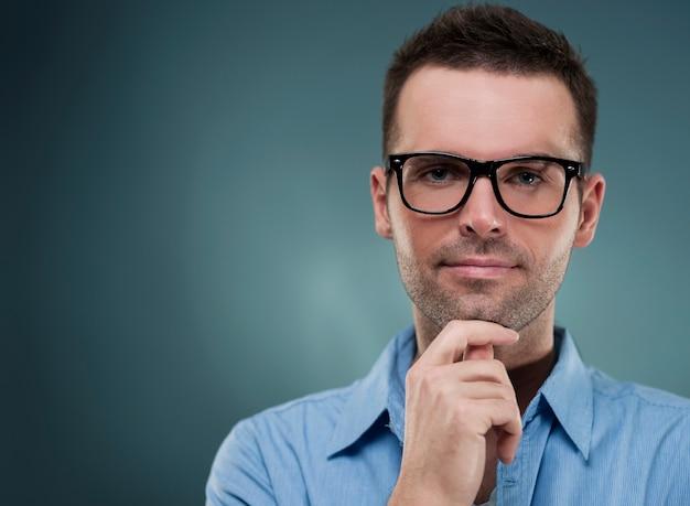 Hombre atractivo con gafas y con la mano en la barbilla