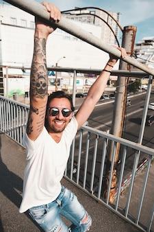 Hombre atractivo con gafas de sol colgando en la ciudad