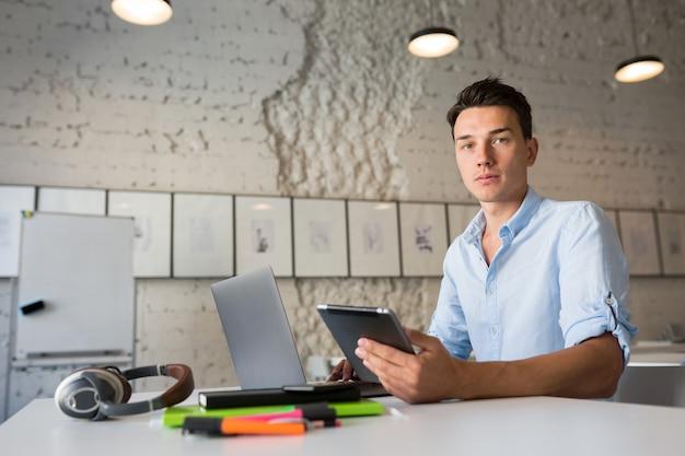 Hombre atractivo hipster usando dispositivos, trabajando en computadora portátil y tableta