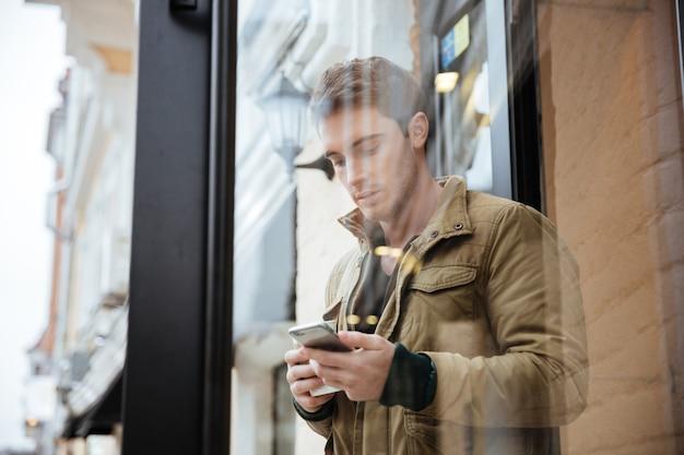Hombre atractivo joven caminando por la calle y charlando por su teléfono al aire libre. mira el teléfono.
