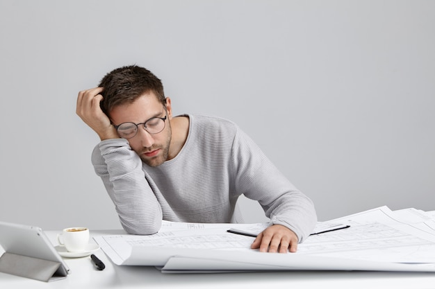 Hombre atractivo joven cansado duerme en el lugar de trabajo, tiene mucho trabajo, está fatigado y agotado