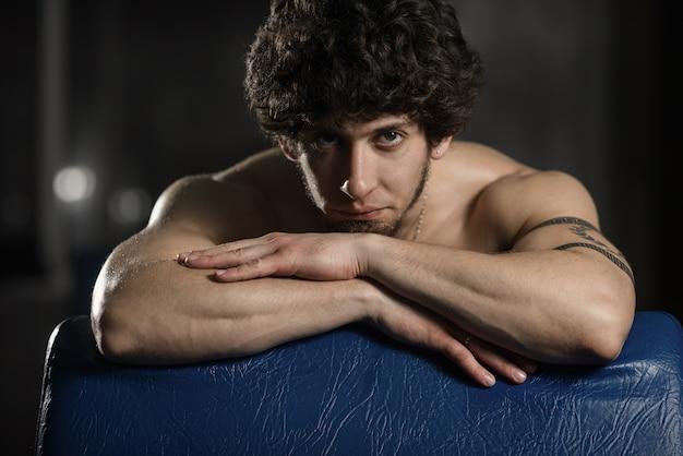 Hombre atractivo joven que descansa en gimnasio después de ejercitar, presentación masculina