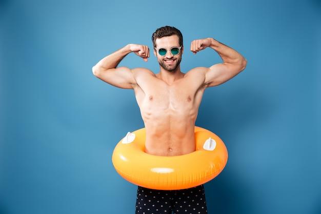 Hombre atractivo joven que muestra sus bíceps