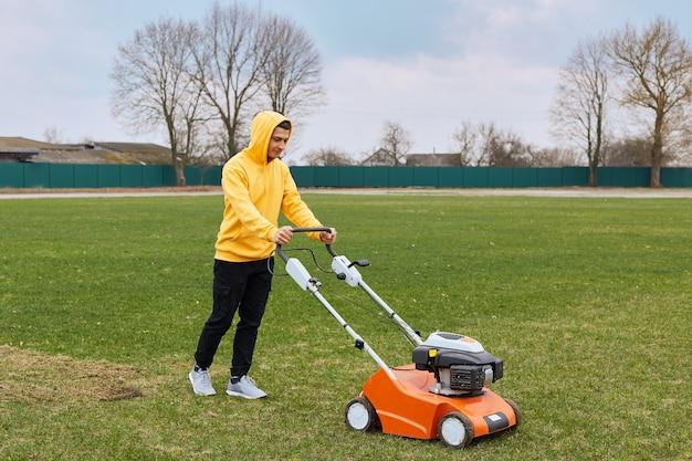 Hombre atractivo joven recortando hierba con cortador
