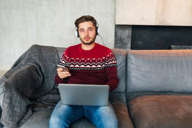 Hombre atractivo joven en el sofá en casa en invierno con el teléfono inteligente en los auriculares, escuchando música, vistiendo un suéter de punto rojo, trabajando en una computadora portátil, autónomo, mirando a la cámara