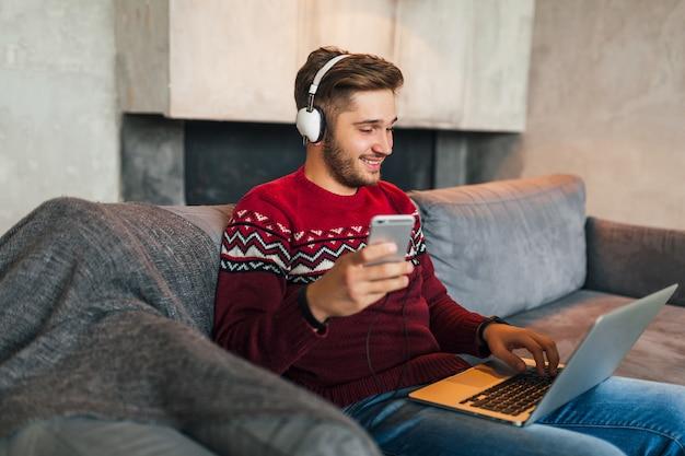 Hombre atractivo joven en el sofá en casa en invierno con el teléfono inteligente en los auriculares, escuchando música, vistiendo un suéter de punto rojo, trabajando en una computadora portátil, autónomo, sonriendo, feliz, positivo, escribiendo