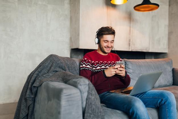 Hombre atractivo joven en el sofá en casa en invierno con el teléfono inteligente en los auriculares, escuchando música, vistiendo suéter de punto rojo, trabajando en la computadora portátil, autónomo